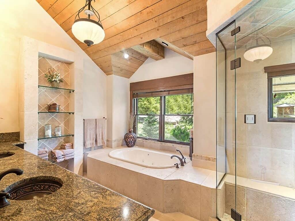 The lovely vanity of this bathroom has brown marble countertops that pairs well with the dark brown basin of the sink with patterns on the side and dark faucets. This matches with the dark faucet of the bathtub that is inlaid with light pink marble tiles.