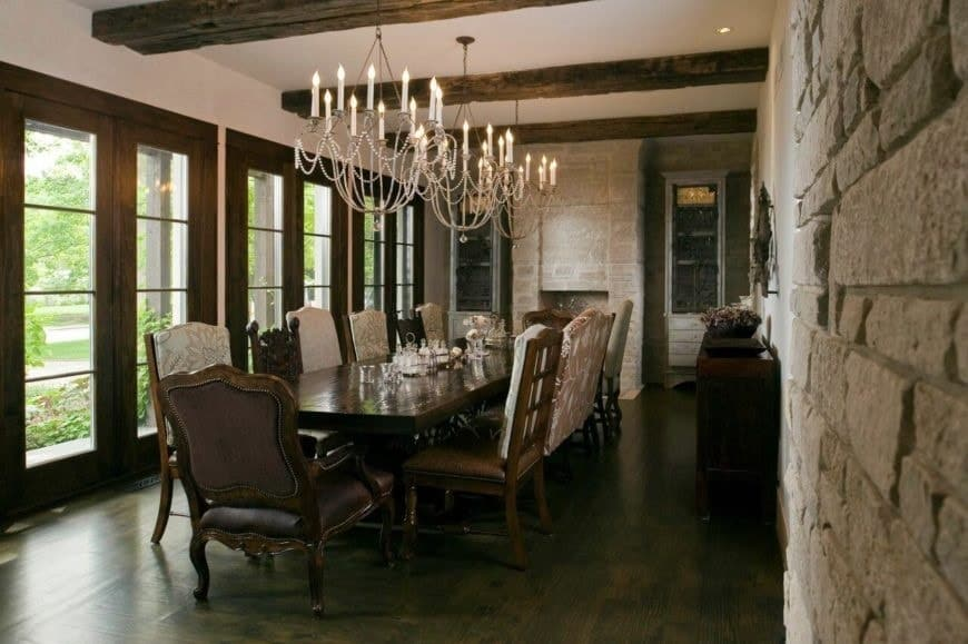 This charming Rustic-style dining room has a large textured stone wall that pairs well with the rustic textured exposed beams on the ceiling that supports a trio of thin white chandeliers hanging over the long dark wooden dining table that pairs well with the dining chairs.