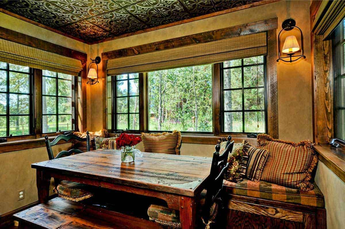 This informal Rustic-style dining area is placed in a charming nook surrounded by windows that feature a lush green scenery outside. There is a built-in wooden bench that has colorful patterned cushions and <a class=