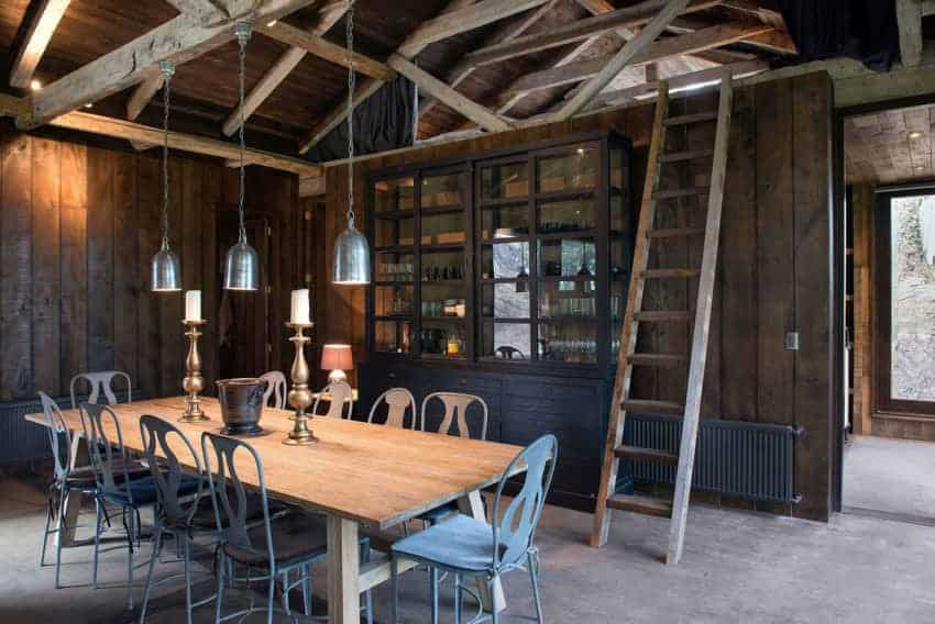 The iron chairs that surround the large wooden dining table have a light hue to them that goes well with the gray concrete flooring and matches with the bell-like pendant lights hanging from the wooden exposed beam of the cathedral ceiling.