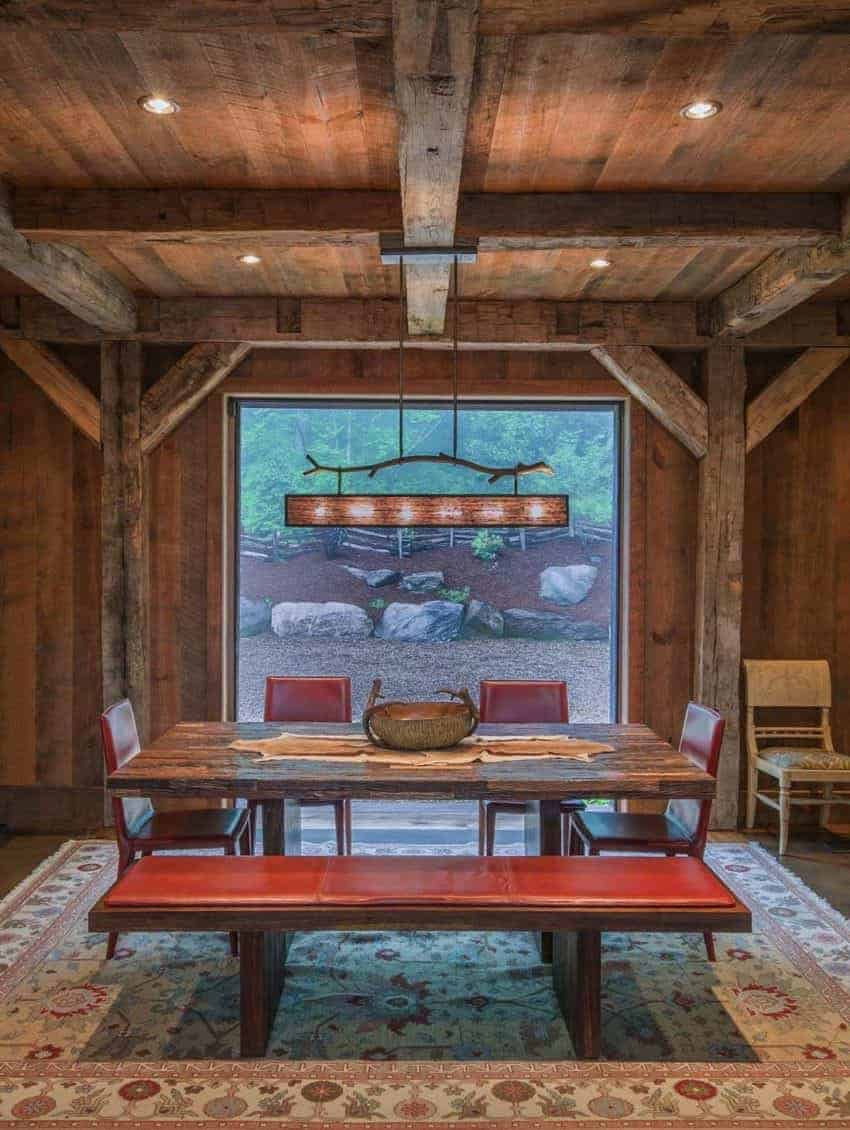 This charming Rustic-style home has a dining room with a wooden dining table that matches the wooden ceiling and its exposed wooden beams that extend to the wooden pillars of the walls the wooden benches and chairs of this table are adorned with red leather cushions.