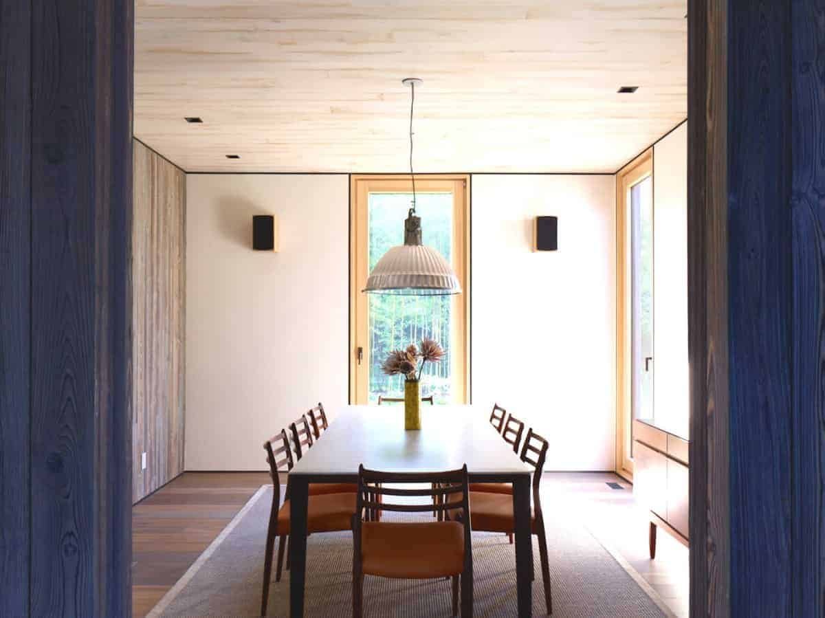 The three wooden surfaces of this Rustic-style dining room has three different shades of wood. The hardwood flooring is the darkest, followed by the wall and the ceiling is the lightest. These are all contrasted by the black dining table and the orange cushions of the chairs.