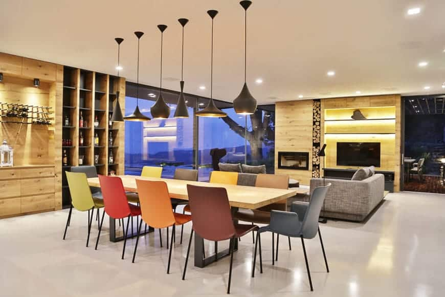 The colorful variety of dining chairs that surround the long wooden dining table gives a colorful contrast to the pure white flooring that matches the ceiling. The wooden walls, on the other hand, matches the hue of the dining table.