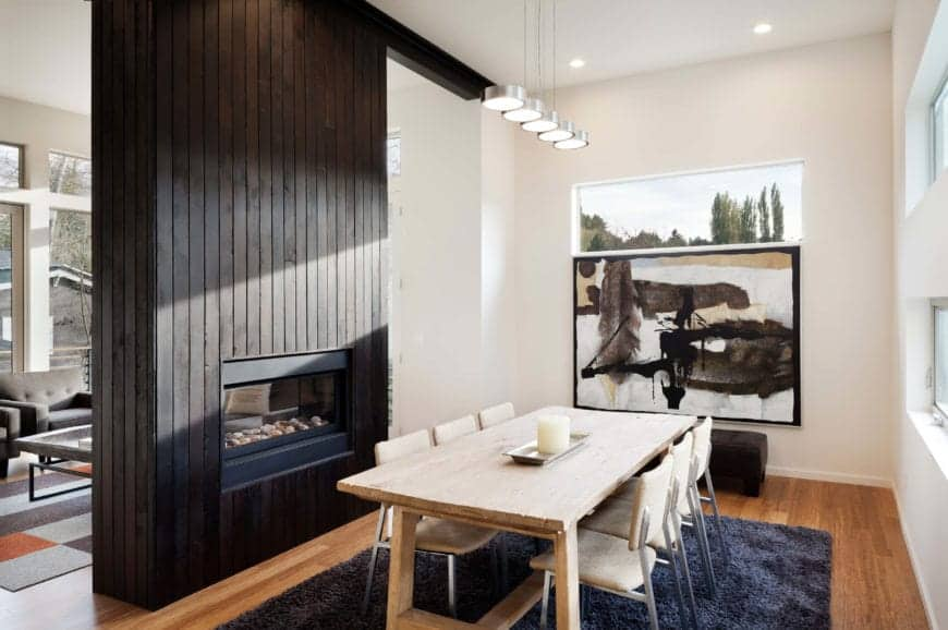 The wooden dining table has a light tone that makes it stand out against the dark blue furry area rug of the hardwood flooring. This small room is adorned with a large painting by the head of the table and a fireplace on the side.