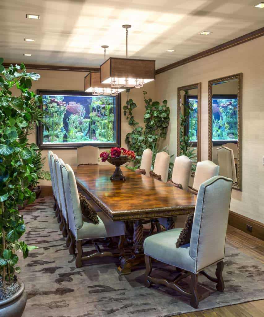This dining room is adorned with potted plants on two corners as well as a brilliantly-lit aquarium by the head of the long wooden dining table with an elegant finish and carvings on the legs. This is paired with beige upholstered dining chairs.