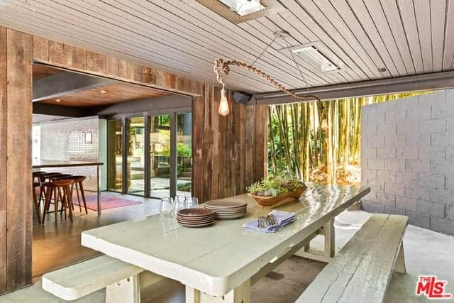 This simple Rustic-style dining area is bathed in sunlight that comes from its open walls. This makes the white wooden dining set shine brighter and also lightens the wooden ceiling that hangs a pair of rustic pendant lights with a rope.