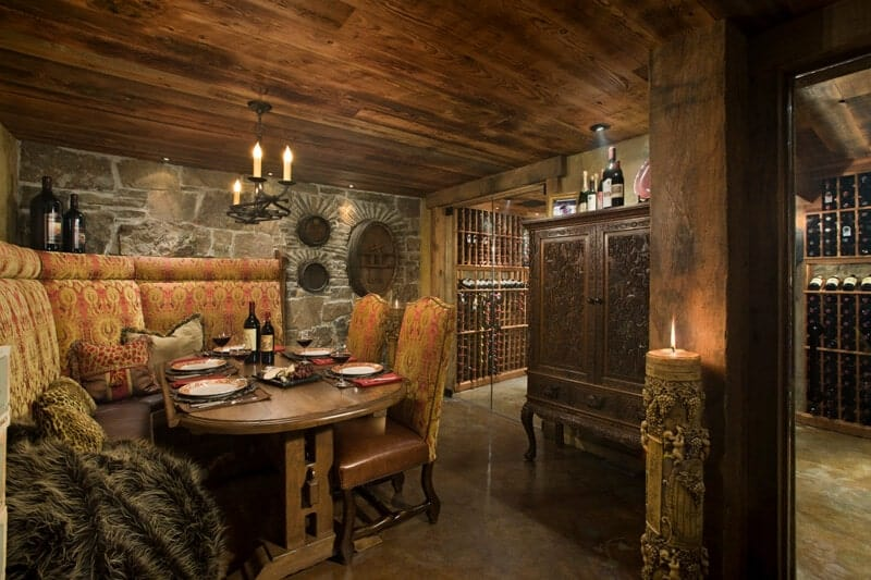 This dungeon-like Rustic-style dining room has a built-in cushioned bench that follows the lay of the gray stone walls that complement the wooden ceiling hanging a small chandelier over the elliptical wooden table and its chairs cushioned the same way as the bench.