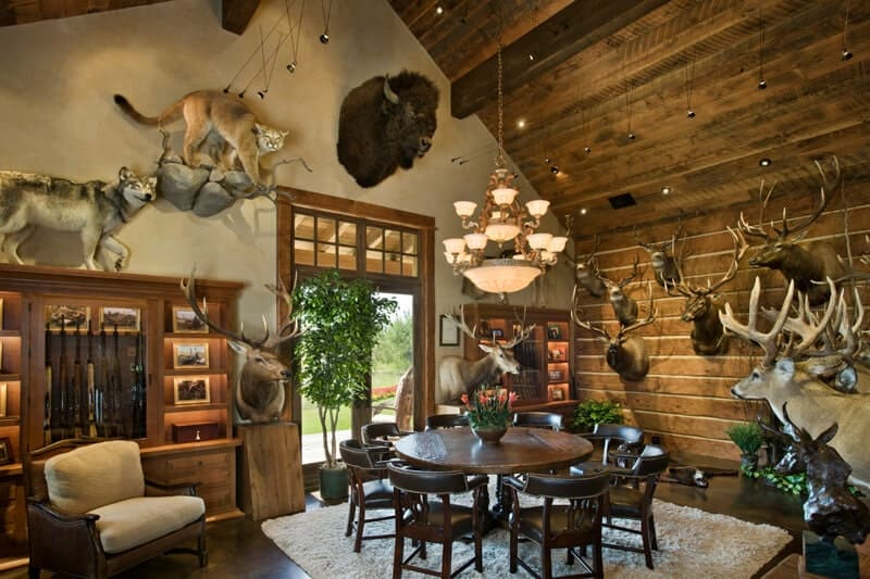 The walls of this Rustic-style dining room is dominated by the menagerie of stuffed animals that set a nice background for the round dark wooden table surrounded by black leather chairs that contrast the white furry area rug underneath.