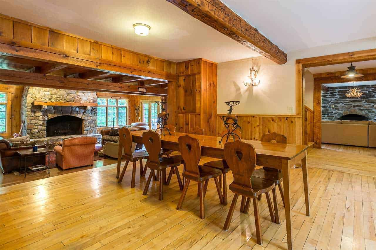 This dining area has a nice background of the living room area that has a large stone fireplace. The dining area has hardwood flooring that blends with the walls as well as the wooden dining set. This also matches with the large exposed beam of the white ceiling.