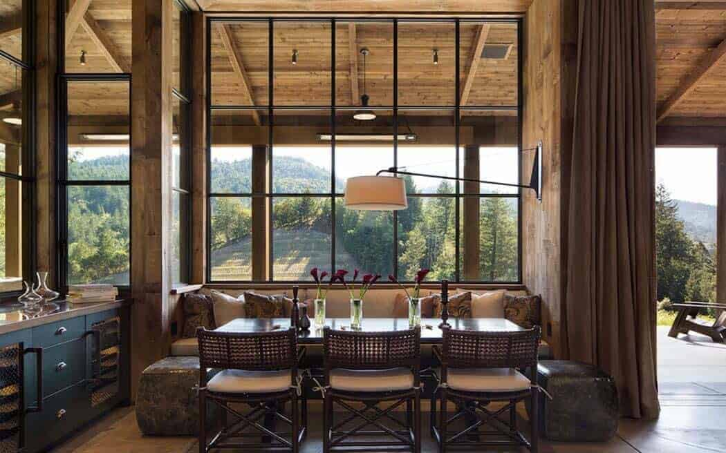 The large windows behind the built-in wooden bench brings in an abundance of natural lighting onto the wooden dining table partnered with bamboo chairs that have woven wicker backs and seats topped with white cushions.