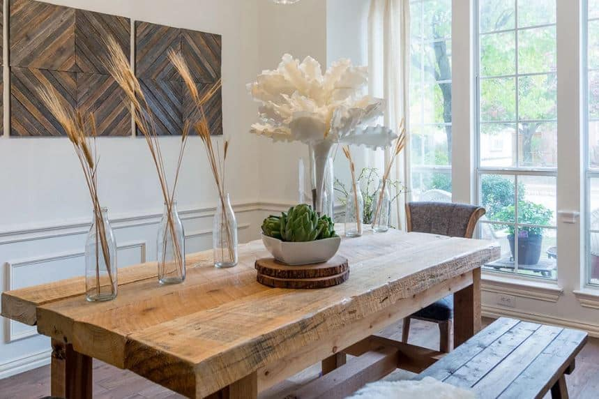 The thick butcher block top of the wooden dining table has a Rustic-style charm to it that matches with the wooden bench. This dining set stands out against the white wainscoting of the walls that is adorned with wall-mounted wooden artworks.