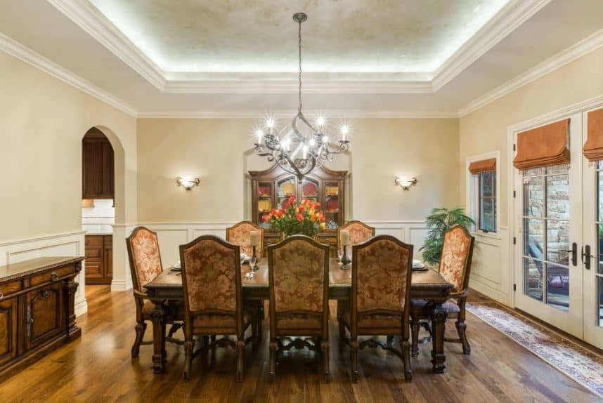 The white tray ceiling has a edging lights that make it glow white. It supports a chandelier over the wooden dining table with an elegant design that matches with the dining chairs upholstered with a chic patterned cushion.