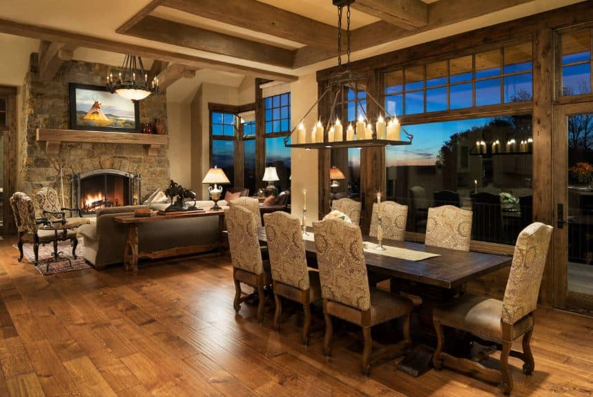 The beige tray ceiling has exposed wooden beams in the middle tray. These beams support a wrought iron structure that supports several candle over the wooden dining table that has a darker hue than the hardwood flooring.