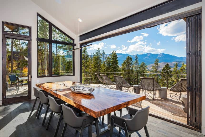 The highlight of this dining area is the wonderful treetop scenery outside presented by the large opening from the folding glass doors. This scenery is enough to complement the simple wooden dining table and its modern dark gray armchairs.