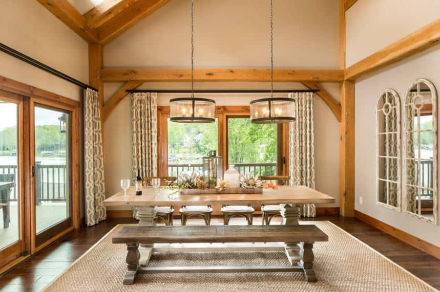 The two round decorative pendant lights are hanging from a high beige shed ceiling that has exposed wooden beams and even a sky light. This beams match with the wooden frames of the sliding glass doors that provide a nice background for the simple wooden dining set.