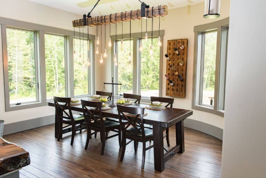 A thick wooden beam hangs from the white ceiling. This supports several pendant lights that brighten up the dark wooden hues of the dining table and chairs that have a darker hue than the hardwood flooring.