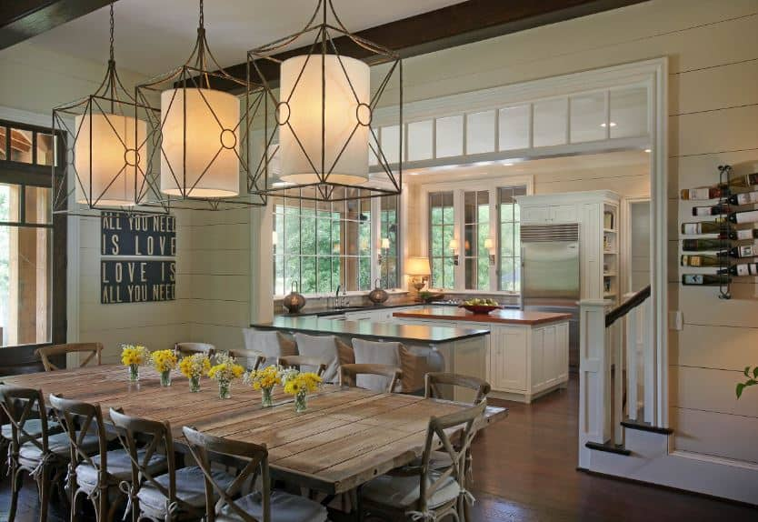 This dining area beside the kitchen has matching dining chairs with a cross-back design. These are all fitted with white cushions that contrast the wooden dining table and the dark hardwood flooring. These are adorned by three decorative lantern-like pendant lights.