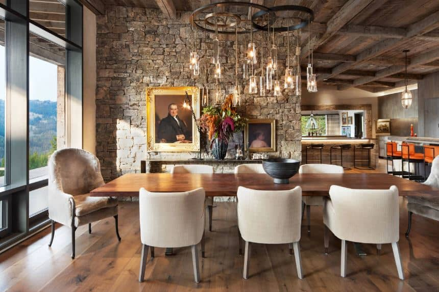 The classic paintings mounted on the textured gray stone wall augments the elegance of this Rustic-style dining area. It has a high ceiling with exposed wooden beams supporting a decorative system of lighting over the long rectangular wooden table.