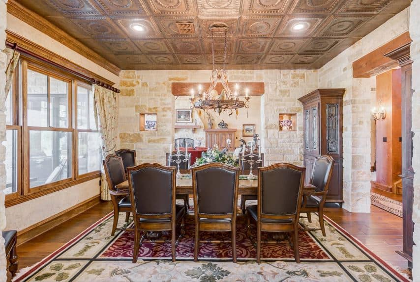 The dark brown wooden ceiling has an embossed pattern on it matching well with the brown design of the hanging chandelier that casts warm light on the wooden dining table and its chairs that are upholstered with gray leather.