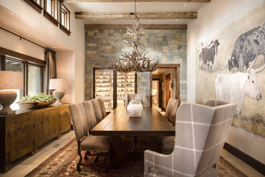 The long wooden dining table has a dark brown hue that is complemented by the patterned area rug covering most of the beige marble flooring. This is paired with a wall dominated by a large mural of bulls augmented by a large antler chandelier.