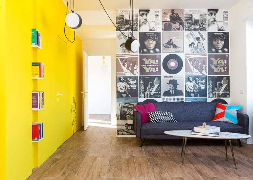 This living room has two distinct walls that contrast each other. One is mustard yellow with a simple depiction of a potted cactus plant and built-in bookshelf. The other is filled with vintage images of the classic blues era album covers paired with a bluish sofa.