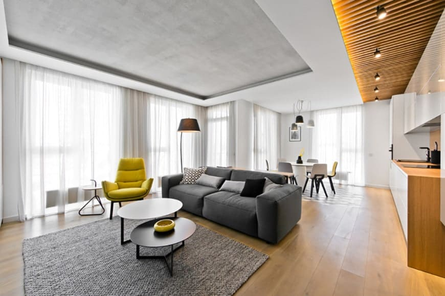 This living room has an airy quality to it due to the bright wide windows paired with a wide light gray tray ceiling. This hue is mirrored on the gray sofa and the woven area rug on the hardwood flooring. The yellow leather armchair stands out against the bright curtained windows.