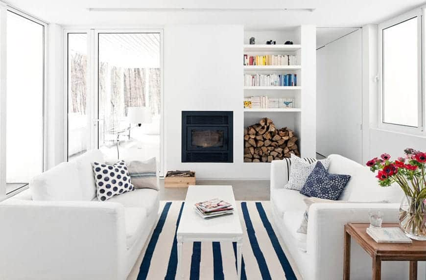 This Scandinavian-Style living room has white walls and a white ceiling paired with white two-seater sofas flanking a white coffee table. The stark brightness of the room is counterbalanced by a blue-striped area rug and a modern fireplace with its stockpile of firewood.