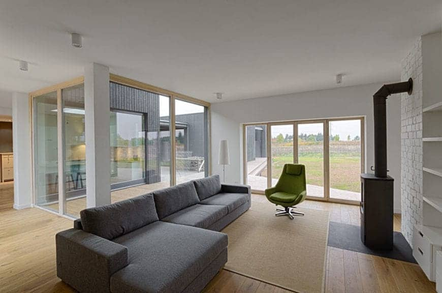 This is a simple and functional living room with its L-shaped comfortable gray sofa facing a small detached dark iron fireplace. The hardwood flooring is paired with multiple glass windows and sliding doors. This gives the bare white walls an accent of abundant views of the serene scene outside.