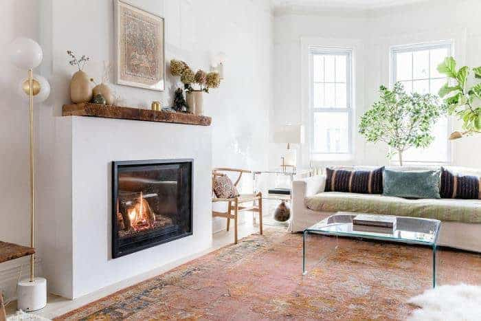 The worn area rug in front of the modern fireplace works well with the brightness of this Scandinavian-Style living room. This same effect is applied to the wall-mounted artwork at the top of the fireplace. The potted tree behind the comfortable sofa is a nice contrast against the tall windows.