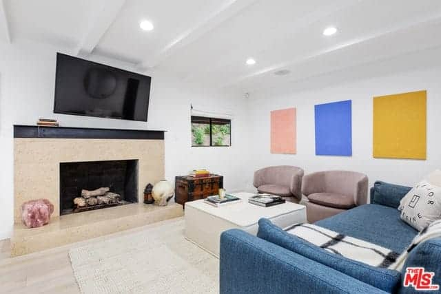 The pastel colors of the wall-mounted artworks play well with the light blue and purple colors of the sofa and cushioned armchairs surrounding the white square coffee table. The fireplace is built into a marble housing that matches with the floor and complements the white ceiling with exposed beams.