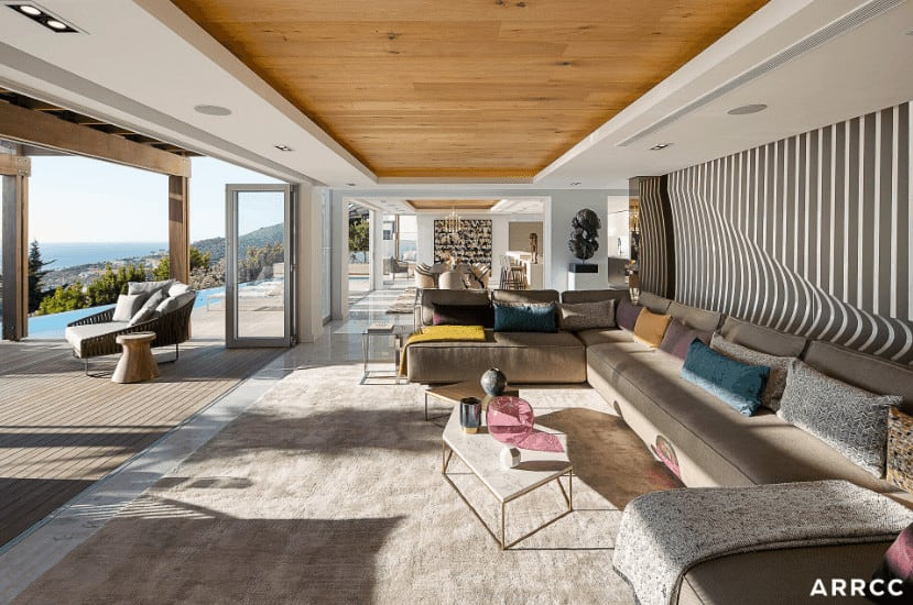 This a spacious living room that has glass doors that open to the outside. This is a visual masterpiece with its tray ceiling with wooden elements and the amazing visual illusion of the wooden finish behind the massive U-shaped gray sofa.