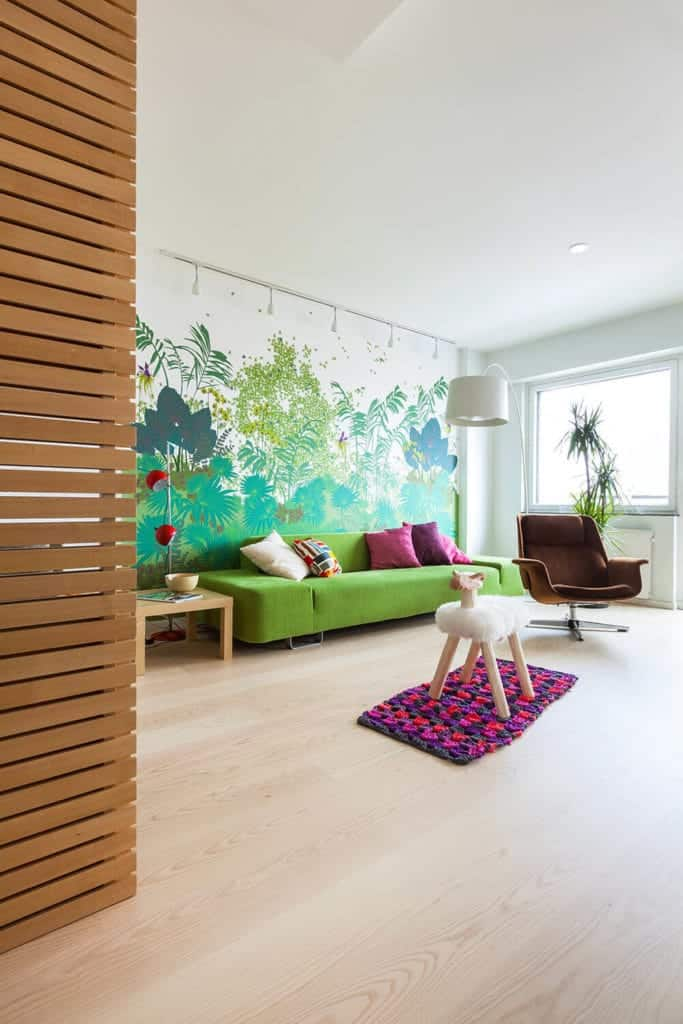 This Scandinavian-Style living room matches its simple and functional design with an explosion of colors that bring life and vibrancy to the white ceiling and hardwood flooring. The beautiful wall mural of nature pairs well with the avocado sofa and brown cushioned armchair.