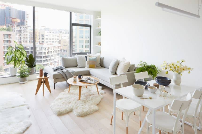 This Scandinavian-Style living shares its space with the dining area that is separated from the living room with a potted plant against the white wall. The massive floor-to-ceiling glass window offers a breathtaking view that you can enjoy from the comfort of an L-shaped light-gray sofa.