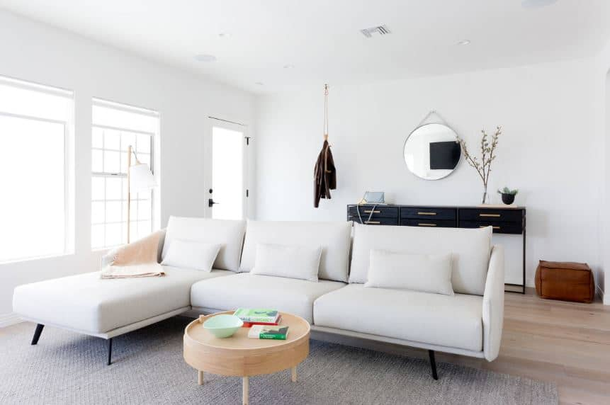 The simple and minimalistic whiteness of the room gives emphasis on the small things like the round wood coffee table in front of the white L-shaped sofa and the leather ottoman at the corner beside the dark wooden console table with drawers.