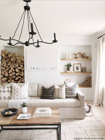 The white wall behind the white sofa of this Scandinavian-Style living room is accented by a framed artwork flanked by a stack of firewood and wooden shelves that hold various decors. On the other hand, the white ceiling is accented by a dark iron simple chandelier.