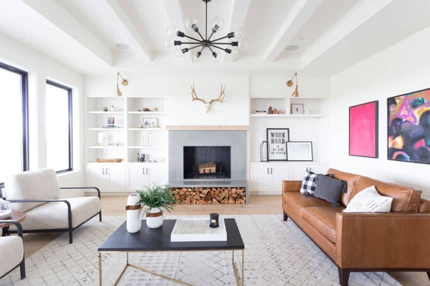 There is a charming dark iron chandelier hanging from the white ceiling with exposed beams. The brown leather sofa is a good match for the hardwood flooring and the stack of firewood beneath the fireplace that is housed in a wall with built-in shelves on both sides.