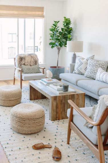 The potted tree at the corner of the white walls is being sustained by the sunlight coming in from the tall windows beside it. The white elements of the area rug, sofa and armchairs are paired with the wooden elements of the coffee table and the two rustic woven ottomans.