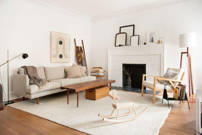 This is a perfect representation of the simple beauty that a Scandinavian-Style living room has. It has a white ceiling and white walls with a fireplace embedded into it with a white housing. The hardwood flooring is topped by a simple white area rug that pairs well with the wooden coffee table and wooden armchair.