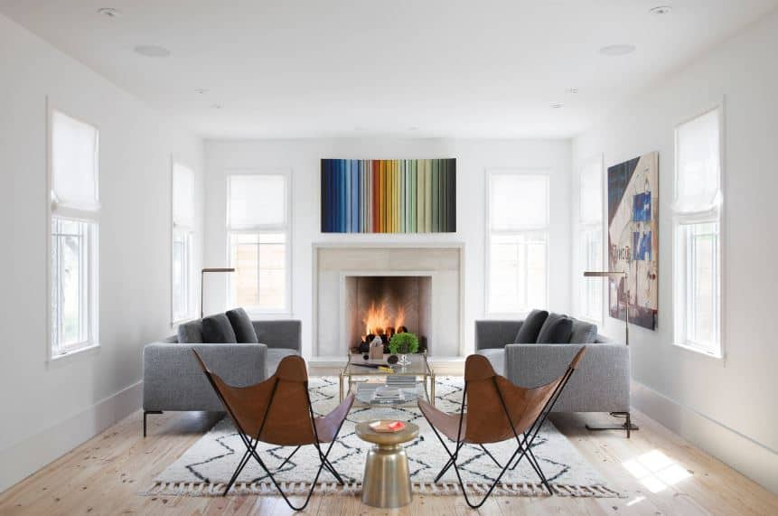 The colorful wall-mounted artworks hanging over the white fireplace and in between the white windows are the stand-out elements of this living room. This is complemented by the symmetry of the gray sofas and hammock-style chairs over the white patterned area rug.