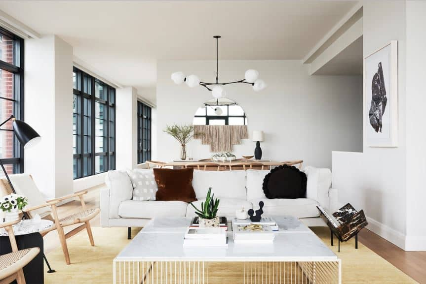 The white walls have massive windows with dark frames. These windows provide natural lighting for the white sofa paired with a modern white coffee table with elegant lines. This is matched with a modern chandelier hanging from the white ceiling.