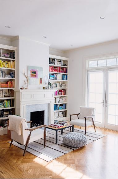 The fireplace is fixed into the white wall with an elegant white wooden finish with a wall-mounted artwork above it. The fireplace is flanked by two bookshelves that are built into the wall. This symmetry is mirrored by the two cushioned armchairs flanking a coffee table over a striped area rug.
