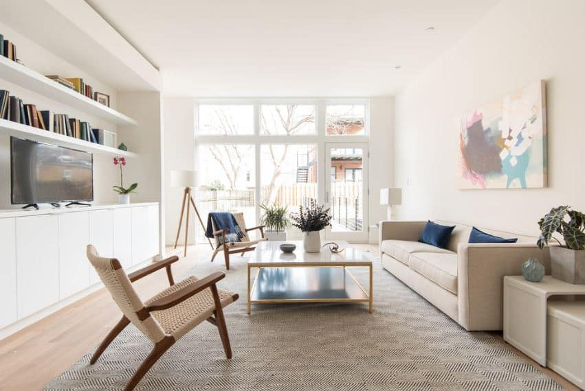 This living room makes the most of the natural light coming from the floor-to-ceiling glass wall that holds a glass door. The natural light illuminates the white ceiling and walls giving emphasis on the beige sofa and the colorful artwork mounted above it.