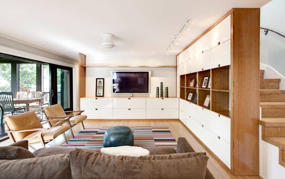 The multi-colored patterned area rug contrasts the plain white ceiling that has a white modern flush lighting mounted in the middle. In front of the brown sofa, a massive wooden structure dominates the adjacent walls with built-in drawers.