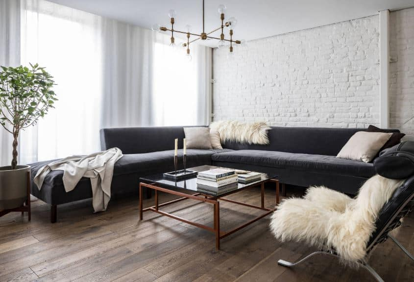 The modern chandelier hanging from the white ceiling mirrors the straight lines of the glass-topped coffee table in front of the L-shaped sofa. The counterbalancing elements here is the potted plant and the white rough stone wall behind the sofa.