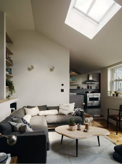 A brilliant sunroof dominates the white shed ceiling in this Scandinavian-Style living room. It illuminates the dark gray tones of the L-shaped sofa against the white wall that have built-in shelves and wall-mounted lamps. A good-looking coffee table stands over a white area rug.