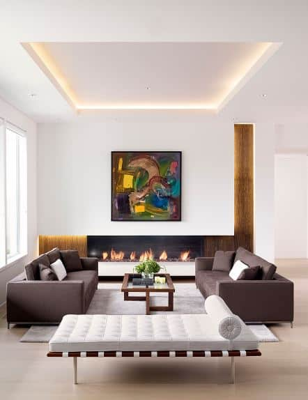 The white tray ceiling matches well with the white walls and white divan by the two gray sofas that flank a modern wooden glass-topped coffee table. There is a wide modern fireplace that is housed in a white wooden structure with a colorful painting mounted above.