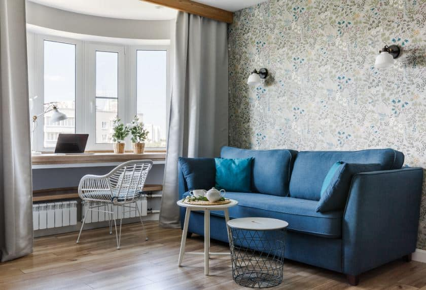 The brilliant blue sofa looks like a comfortable embrace of blue waters against the hardwood flooring and the flowery wallpaper behind the sofa. There is a couple of wall-mounted lamps at the top of the sofa for illumination by the windows of the office area.