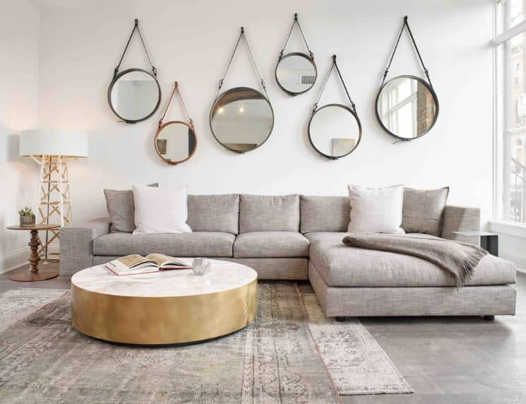 This Scandinavian-Style living room has a theme of circles that are dominating on the circular mirrors mounted on the white wall above the gray L-shaped sofa and the charming cylindrical wooden coffee table over the light-hued patterned area rugs.