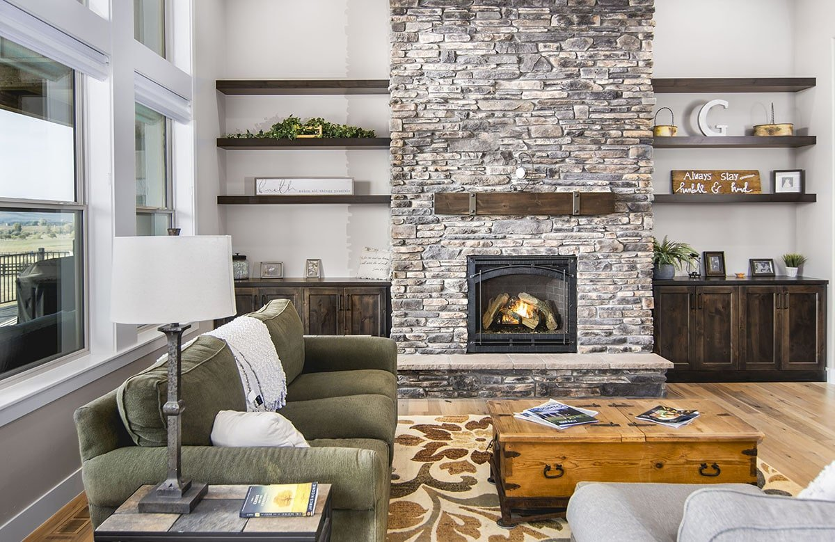 Living room with fabric seats, a trunk chest coffee table, and a stone fireplace flanked by dark wood cabinets and floating shelves. Large windows on the left wall bring in an abundant amount of natural light.