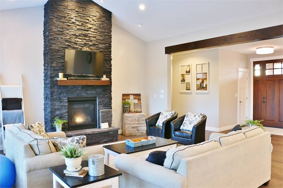 A stone fireplace sets a striking focal point while small potted plants bring a refreshing ambiance to this living room